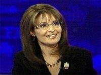 Closeup of Sarah smiling - black dress - blue background