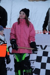Piper holding checkered flag to wave her Dad into the 2011 Iron Dog finish line