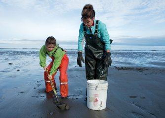 Sarah and Piper hunting clams on beach