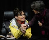Sarah clasps hand of woman at Anchorage book signing