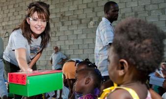Sarah handing shoebox gift package to Haitian child