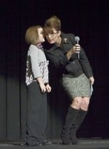 Sarah holding microphone and leaning to listen to Piper