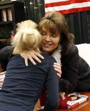 Sarah hugs young girl at Cincinnati book signing