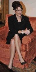 Sarah in black dress sitting in armchair