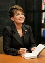 Sarah in black suit signing book in Baton Rouge