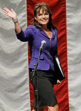 Sarah in purple jacket waving and carrying notebook