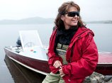 Sarah in red jacket and wearing sunglasses and sitting on boat