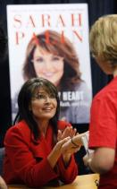 Sarah in red outfit at table in front of Poster at Book Signing