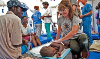Sarah sitting on cot with sick Haitian child