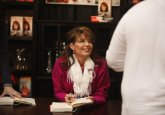 Sarah talking to someone as she signs book in Andover KS