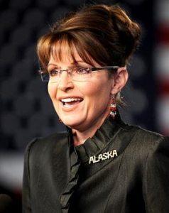Closeup of Sarah smiling in black jacket with Alaska emblem