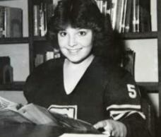 High school photo of Sarah in team sweatshirt in library