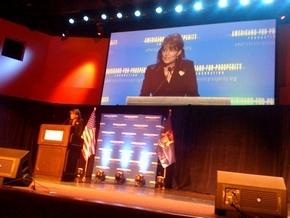 Monitor Screen of Sarah Addressing Defending the American Dream Summit in Michigan