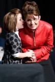 Piper whispering in Sarah's ear