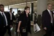 Sarah arriving at check-in counter at Hong Kong airport after her speech