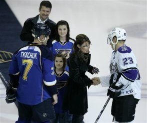 Sarah holds hockey puck in St, Louis