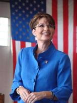 Sarah in blue jacket in front of flag