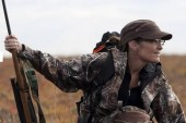 Sarah in camo with rifle on tundra during hunting trip