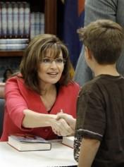 Sarah in Fuchsia jacket shaking young boy's hand