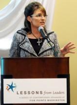 Sarah in gray plaid jacket speaking in Washington Ilinois