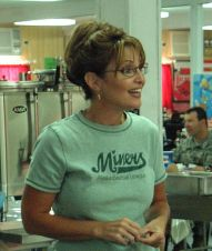 Sarah in green Miners t-shirt talking to troops