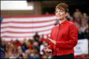 Sarah in red jacket clapping with flag in distant background