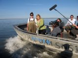 Sarah in waders in boat with news crew