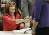 Sarah shaking hands with supporter at book signing table in Tempe AZ