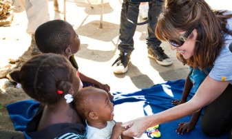 Sarah smiling at Haitian child