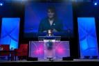 Sarah speaking in Vegas beneath big screen