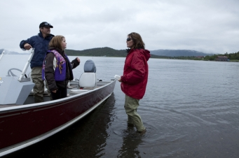 Sarah standing next to boat with Todd and Piper in it
