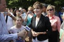 Sarah talking to reporters during bus tour - Piper beside her