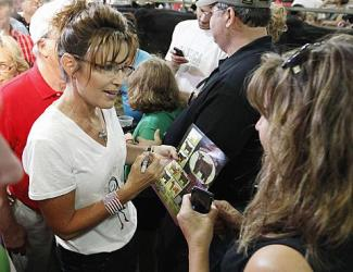 Sarah talks with girl as she autographs photo at Iowa state fair