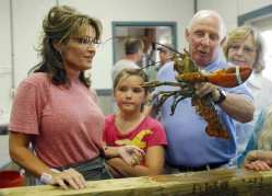 Former Alaska Governor Palin watches as her father Chuck Heath hold up a lobster during a visit to Yankee Seafood Cooperative in Seabrook
