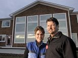 Todd and Sarah in activewear outside their Alaska home
