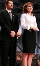 Todd and Sarah - standing - Todd in suit - Sarah in white blouse and skirt