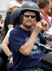 Todd fastens motorcycle helmet at Rolling Thunder rally in DC - Piper behind him on bike