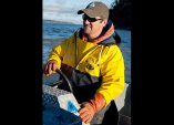 Todd in yellow jacket on boat