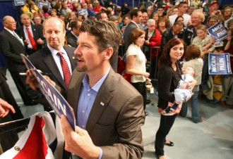 Willow holds Trig and looks on as Todd signs campaign sign at welcome home rally in Fairbanks after VP announcement