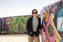Bristol in sunglasses and sweatshirt beside rug display