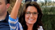 Closeup of Sarah smiling with arm raised at Kirk Adams rally