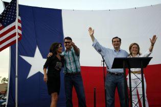 Cruzes at podium waving and Todd pointing with arm around Sarah
