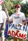 Lady wearing I heart Sarah Palin t-shirt and holding flag and Palin + Adams sign