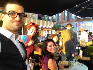 Mark Ballas clowning as Bristol sits at a table in the background
