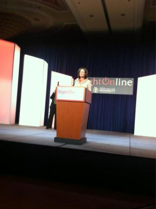 Photo of Sarah behind podium onstage at - Malkin