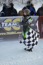 Piper holds flags at finish line of 2012 Iron Dog Race
