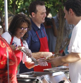 Sarah and Kirk Adams smile as they serve BBQ