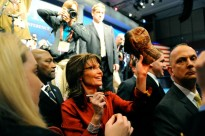 Sarah autographing cap for someone in crowd at CPAC