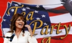 Sarah lifts hand toward mouth while speaking in front of Tea Party sign in Iowa