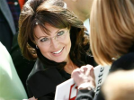 Sarah looking upward at supporter while autographing